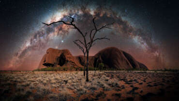 Uluru`s Night von Nacht- und Astrofotograf Stefan Liebermann - Night Panorama of the Uluru in Australia. In the foreground you can spot burned down trees and contrast between dry gras and burned down regions. In the sky is the milky way arch.